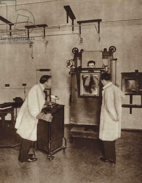 Man having a chest X-ray (b/w photo)