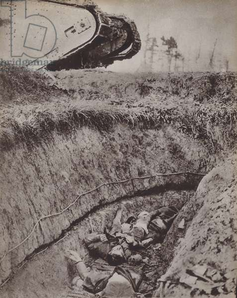 British tank passing over a trench containing the bodies of dead soldiers, World War I (b/w photo)