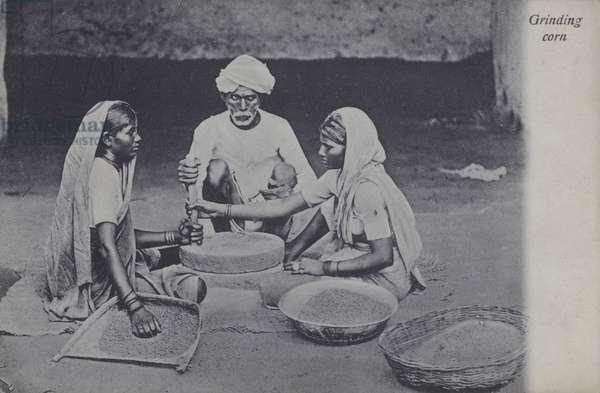 Man and women grinding corn, North Africa (b/w photo)