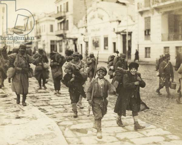Scenes in Salonika, showing boys being allowed to carry the equipment of newly landed French soldiers (b/w photo)