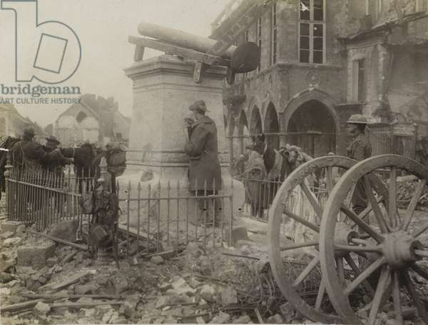 Australian soldier writing his name on the pedestal of a statue in Square in Bapaume (b/w photo)