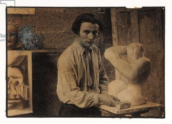 Henri Gaudier-Brzeska standing behind 'Seated Woman', c. 1914 (sepia print)