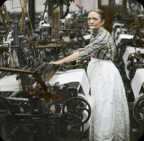 Older woman in pinafore stands at a loom in a textile mill, probably Leeds, 1905-15 (colour lantern slide)