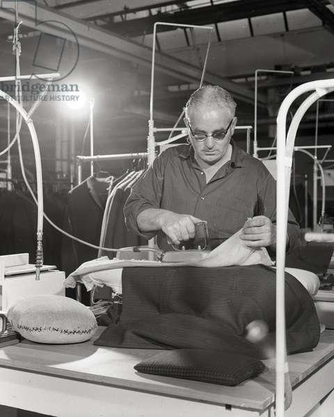 Man at work on hand pressing machine, Burton's tailors, England, 1966 (b/w photo)