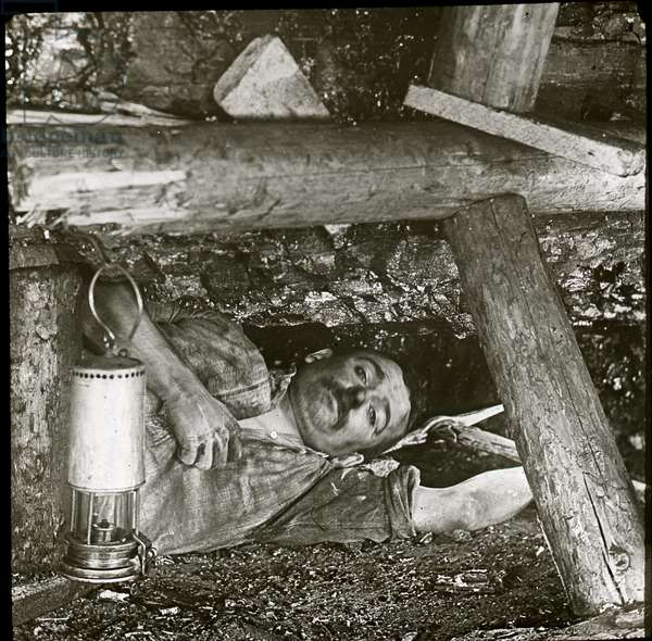 View of miner lying beneath coal seam behind pit prop with Davy lamp in front, 1909 (b/w photo)