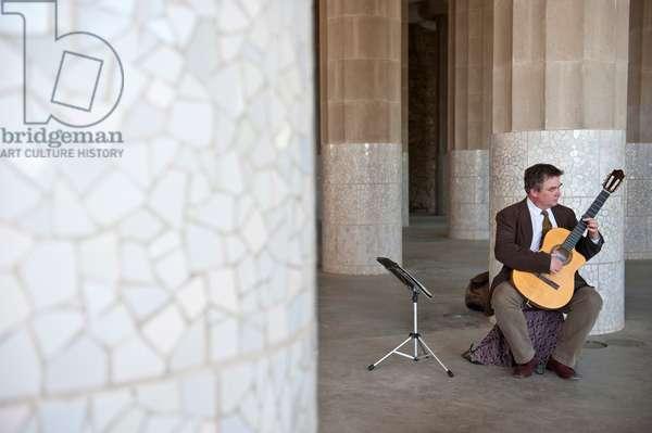 Musician playing guitar in the Güell park, Barcelona, Catalonia, Spain