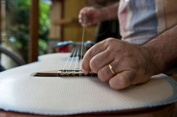 Master Luthier (Guitar-Maker) in his workshop in the process of making a classical Spanish guitar