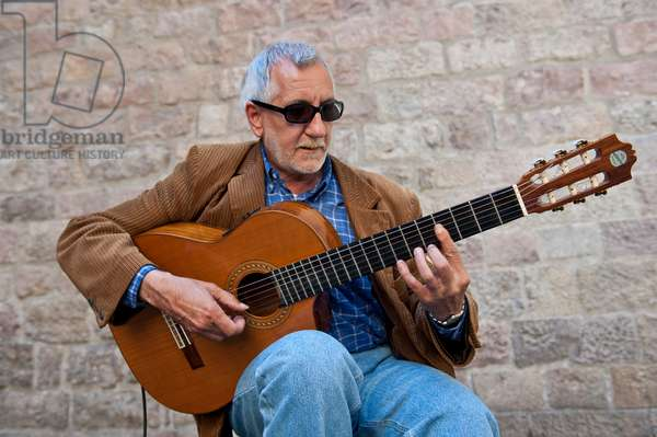 Spanish guitar palyer performing in the street of the Gothic area of Barcelona, Spain
