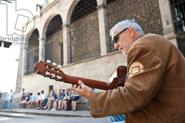 Spanish guitar player performing in the street of the Gothic area of Barcelona, Spain