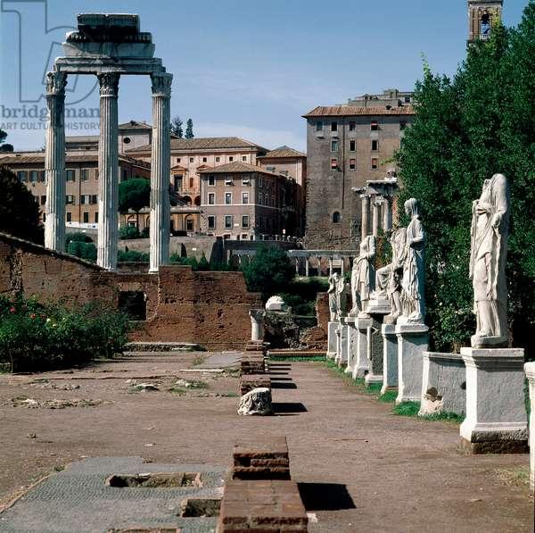 Roman Forum: statues of vestals. House of vestals (Casa delle Vestali or Atrium Vestae). On the left, the Greek temple of Dioscures (or temple of Castor and Pollux) (5th century BC). Rome