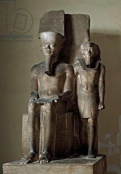 Pharaoh Tutankhamun standing near the divinite Amon-Ra on the throne, 600 BC (calcite sculpture)