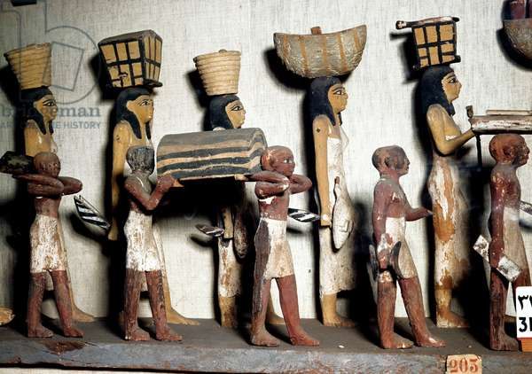 Egyptian antiquite: a sculpted group of painted wood representing servants bearing offerings to the deceased. Cairo, Egyptian Museum