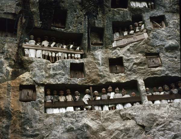 View of a stone-carved animist burial site. Tau tau (effigies of the deceased) were put in the cave, looking out over the land