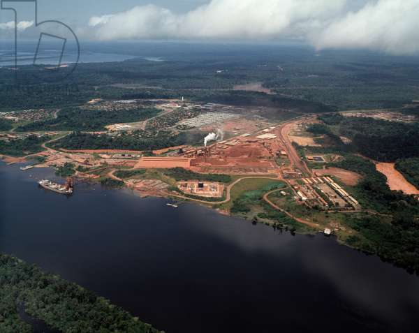 Air view of the bauxite mines along the Trombetas River operated by Mineracao Alcan, workers' housing and loading docks are visible, State of Para, Brazil - Aerial view of bauxite mines alongside Trombetas river with loading pier and workers housing, Brazil, 1983 - Photography