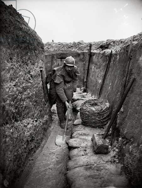 Soldier cleaning a trench in the Champagne region, 1915-16 (b/w photo)