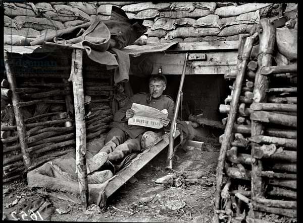 Soldier reading 'Notre Belgique' in his trench, 1917 (b/w photo)