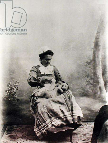 Nanny showing how to dress a baby, c.1900-05 (b/w photo)