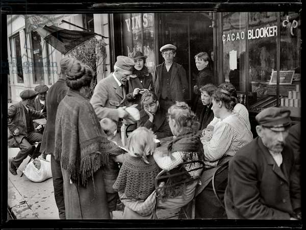 Refugees being given some bread on arrival in Paris, 1914 (b/w photo)
