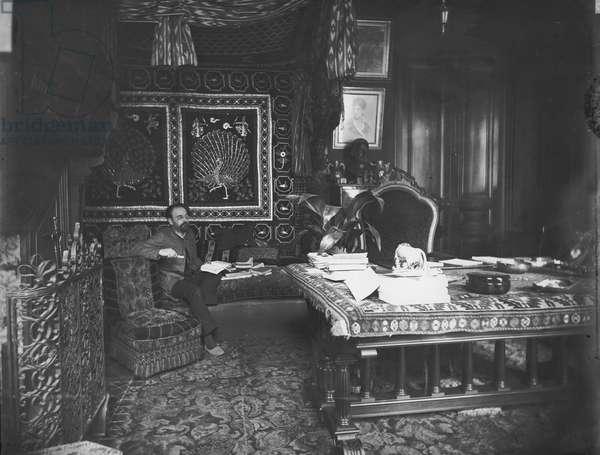 Portrait of Emile Zola (1840-1902) seated on his sofa (b/w photo)