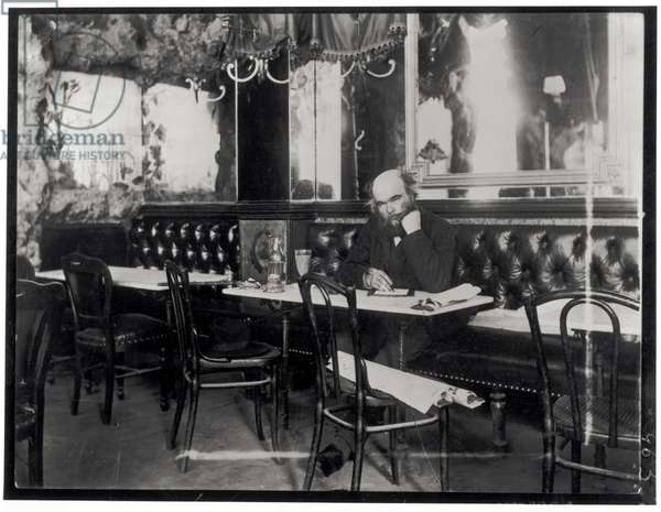 Paul Verlaine (1844-96) writing at a table in a cafe (b/w photo)