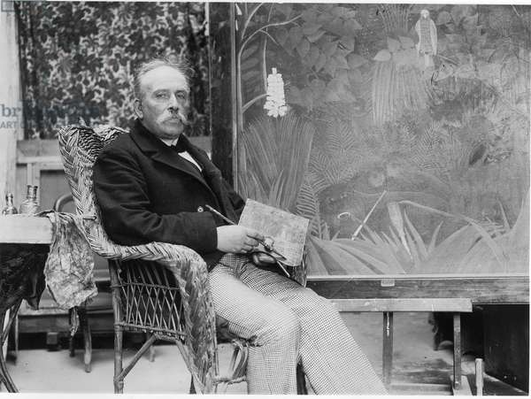 Henri (Le Douanier) Rousseau (1844-1910) in front of his painting 'The Merry Jesters', in his studio at rue Perrel, Paris, c.1907 (b/w photo)