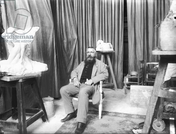 Auguste Rodin (1840-1917) seated beside the sculpture 'Le Printemps' (Eternal Spring) in his studio (b/w photo)