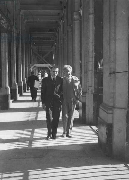 Jean Cocteau in a Palais Royal arcade with his friend René Bailly, editor at Larousse, 1957 (b/w photo)