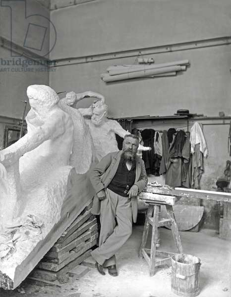 Auguste Rodin (1840-1917) beside his work in his studio (b/w photo)