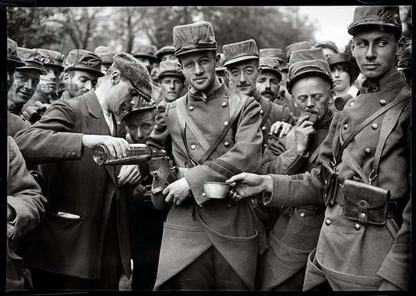 A civilian giving a drink to soldiers, 1914 (b/w photo)