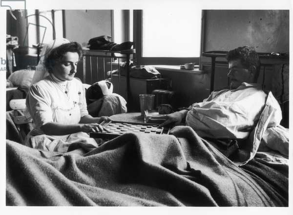 A Red Cross nurse playing draughts with a patient, 1914 (b/w photo)