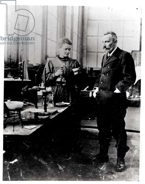 Pierre (1859-1906) and Marie Curie (1867-1934) in their laboratory, c.1900 (b/w photo)