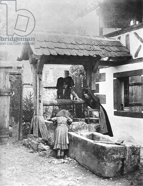 Young Alsatian girls at the well, after 1855 (b/w photo)