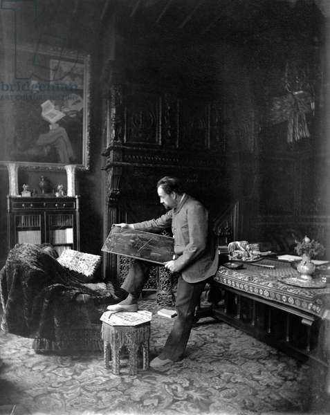 Portrait of Emile Zola (1840-1902) looking at a painting in his study (b/w photo)