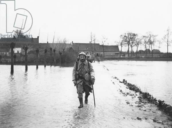 Soldier crossing a flooded road, Yser, 1915 (b/w photo)