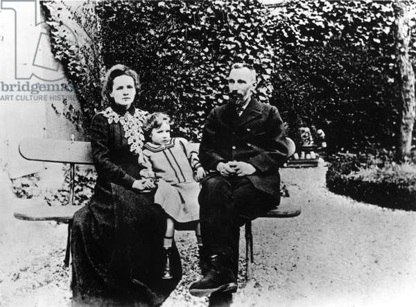 Pierre (1859-1906) and Marie Curie (1867-1934) sitting on a bench in a garden.