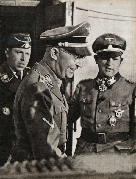 """The Reichsfuhrer SS Heinrich Himmler (1900-1945) visiting the Russian front, reviews Hitler's personal guard, the Leibstandarte SS - Behind him, the general of the Waffen SS Sepp Dietrich (1892-1966) and on the left, the commander of the blindee division - Photography in """""""" die Woche"""" 1/09/1943 - Selva Collection"""