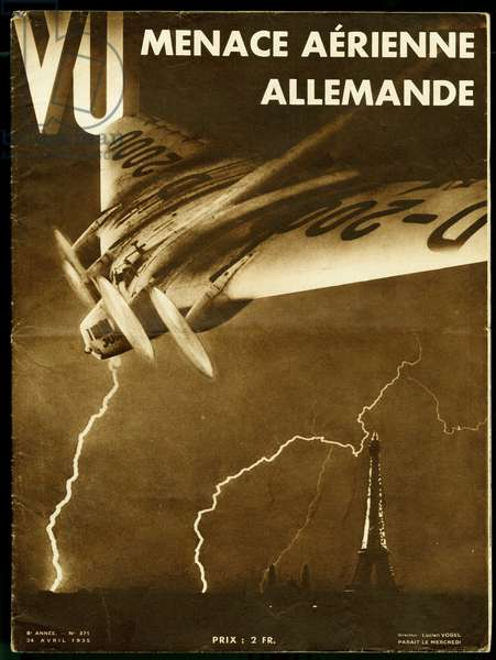 A German warplane flies over Paris and the Eiffel Tower, in the midst of the lights crossing the sky, an illustration for a report on German air mobilization. Photomontage for the cover of the weekly VU, director Lucien Vogel, number 371, date 24/4/1935. Selva Collection.