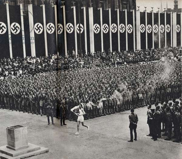 """The Olympic torch bearer arrives in the Lustgarten, Berlin, and lights the fire of the altar, which will burn until 16 August, closing date of the Olympic Games - Photography in """""""" die Woche"""""""", special number for summer 1936 - Selva Collection"""