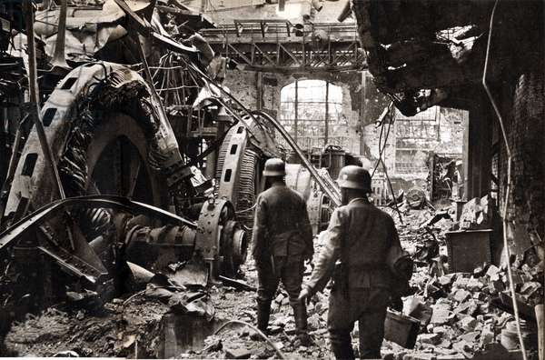 """Inside a ruined workshop in Stalingrad (present-day Volgograd), two German grenadiers inspect the destroyed energy generator - Photography in """""""" die Woche"""""""" 2/12/1942 - Selva Collection"""