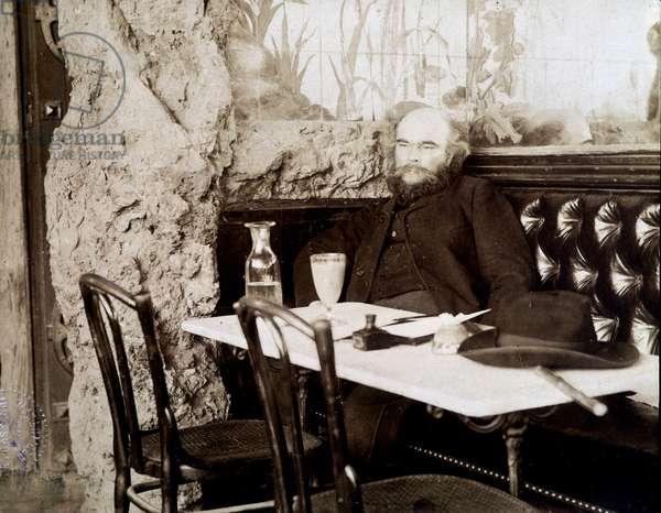Verlaine in a bistro drinking absinthe