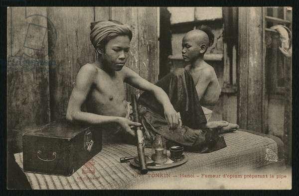 Postcard depicting an opium smoker preparing the pipe, Tonkin, Hanoi, c.1900 (b/w photo)