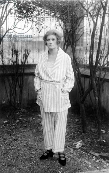 France: Young woman poses in pajamas in her garden, 1925