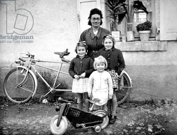 France: a woman and her three daughters with a tandem and a bicycle, children's toys, 1950