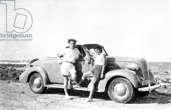 Africa: Decapotable car in the African bush with young couple sitting on the hood, 1947 -