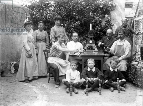 France: A family of peasants poses outside a souvenir of the Eiffel tower in thermometer on a garden table, 1895