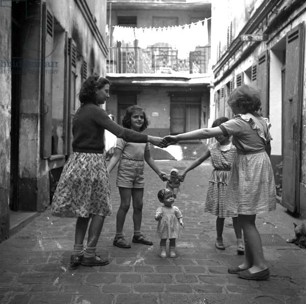 France, Ile-de-France, Paris (75): in a building course, four little girls make a round around a doll, 1945