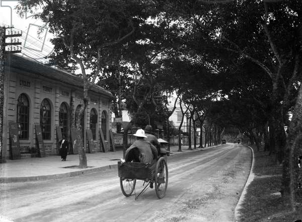 Indochina/Vietnam, Haiphong: In Felix Faure Boulevard a rickshaw carries two passengers, 1900