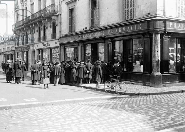 France, Centre, Indre-et-Loire (37), Tours: avenue Grammont, a tail in front of a food trade, 1917 - shops: Van Pee, dyeing shop of the avenue, butter and cheese RaassFrere, pharmacy store
