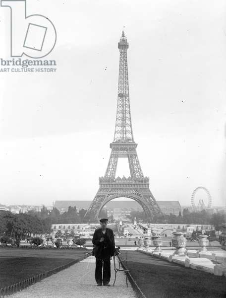 France, Ile-de-France, Paris (75): A man poses in front of the Eiffel Tower during the World Exhibition, 1900