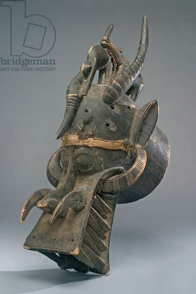 Helmet mask of the Senufo people (Cote d'Ivoire) (wood, cotton, feathers, iron, leather & pigment)
